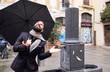 un hombre con barba mira si ha parado de llover en una plaza