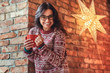 Portrait of a cheerful brunette girl wearing eyeglasses and warm sweater holding a cup of coffee while leaning on a brick wall.