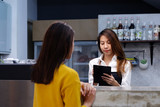 Young asian woman barista taking note, order, at coffee cafe counter with smiling face, food and drink business concept