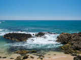 Beautiful rocky beach on sunny day with clear blue water and blue cloudless sky in Vila do Conde, Porto region, Portugal