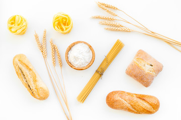 Products made of wheat flour. White flour in bowl, wheat ears, fresh bread and raw pasta on white background top view