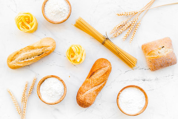 Products made of wheat flour. White flour in bowl, wheat ears, fresh bread and raw pasta on white stone background top view