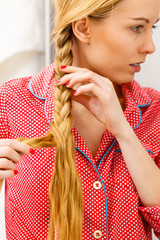 Woman doing braid on blonde hair © Voyagerix