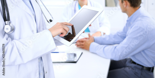 Leinwandbild Motiv Doctor using tablet computer, close-up of hands at touch pad screen. Patient is at the background