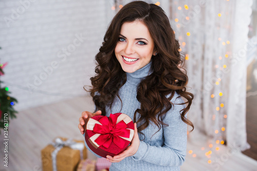 Beautiful woman with a gift on New Year's Eve.