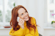 Cheerful red-haired woman talking on phone