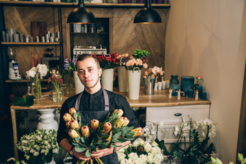 Portrait of male owner with lush bouquet of king Protea, assortment different flowers on wooden counter behind him. Man florist holding a flowers arrangements in modern interior floral butique