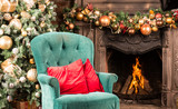 Christmas room, firewood burning in the fireplace, a green armchair with red pillows and a Christmas tree with gifts