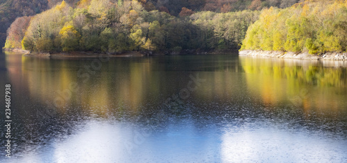 The forest in autumn is reflected in the Endara reservoir, Navarra