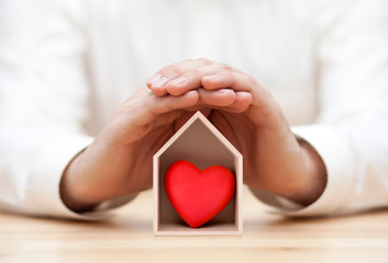 Wooden house with red heart protected by hands