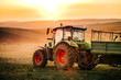 Leinwandbild Motiv Details of farmer working in the fields with tractor on a sunset background. Agriculture industry details
