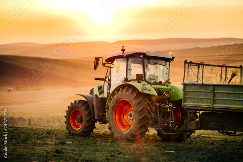 Leinwanddruck Bild Details of farmer working in the fields with tractor on a sunset background. Agriculture industry details