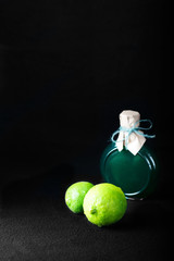 LIME ON A BLACK BACKGROUND WITH A BOTTLE OF LIME OIL