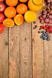 Orange juice, fresh oranges, apples, grapes, raspberries and blueberries on a wooden table - fruit background - view from above - vertical photo