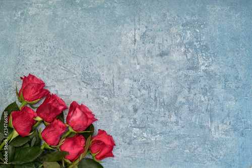 Bouquet of red roses on blue background. Top view, copy space.