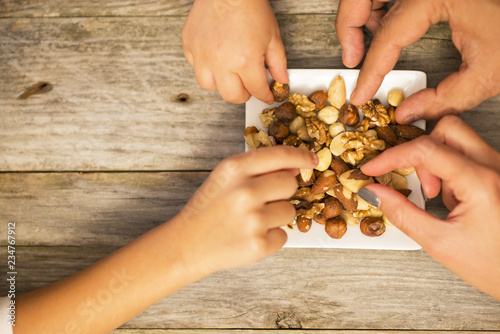 fototapeta na ścianę Four members family picking mixed nuts from white plate