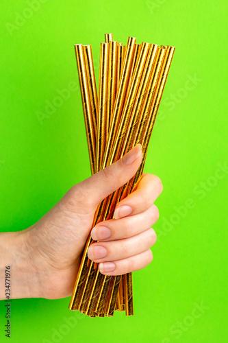 Leinwandbild Motiv Woman is holding golden paper straws in hand