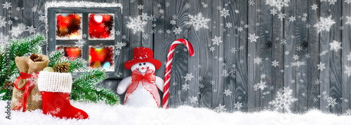 Leinwandbild Motiv Santa boot with gifts and Snowman on wooden wall background and glowing window