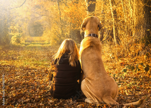 Leinwandbild Motiv Beste Freunde Kind und Hund sitzen glücklich zusammen im leuchtenden Herbstwald