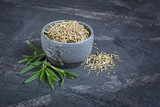Gray handcrafted pottery bowl full of dried spice with green leaves rosemary - 234831583