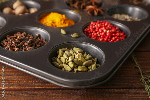 Different aromatic spices in holder on wooden table, closeup
