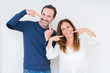 Leinwanddruck Bild - Beautiful middle age couple in love over isolated background smiling confident showing and pointing with fingers teeth and mouth. Health concept.