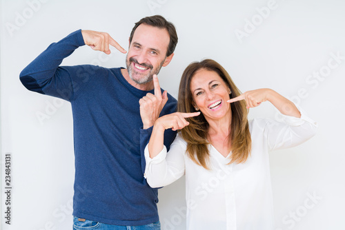 Leinwanddruck Bild Beautiful middle age couple in love over isolated background smiling confident showing and pointing with fingers teeth and mouth. Health concept.