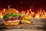 Delicious hamburger with fire on background - 234843976