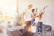 Leinwandbild Motiv Kinder helfen Vater beim Wand streichen in Haus