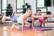 Leinwandbild Motiv junge leute menschen machen sport fitness im fitnessstudio auf der matte, dehnen halteübungen rumpftraining