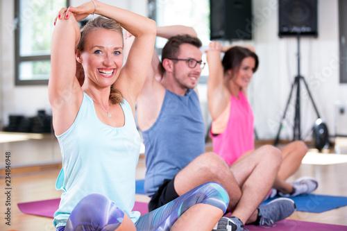 Leinwanddruck Bild junge leute menschen machen sport fitness im fitnessstudio auf der matte, dehnen halteübungen rumpftraining