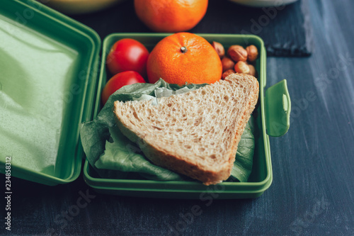 Foto Murales School lunch boxes with sandwich and fresh vegetables, nuts and fruits on blackbackground. Healthy eating concept.