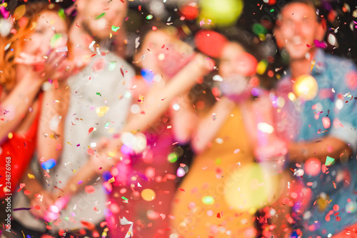 Blurred people making party throwing confetti - Young people celebrating on weekend night - Entertainment, fun, new year's eve, nightlife and fest concept - Defocused photo - 234876963