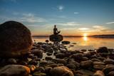 hübsche junge frau macht yoga auf einem Stein im Wasser See Meer im Sonnenuntergang Abendrot