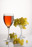 glass of wine and a bunch of ripe grapes on white background