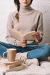 cup of hot chocolate with marshmallows and girl reading book behind