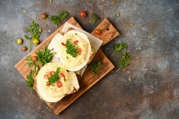 Mashed celery root on wooden cutting board on dark background. Horizontal.