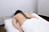 A woman in a clinic receiving hot stone massage. Back view