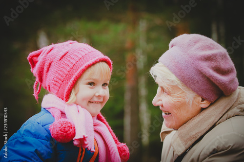 Leinwandbild Motiv happy grandmother and granddaughter talk in nature
