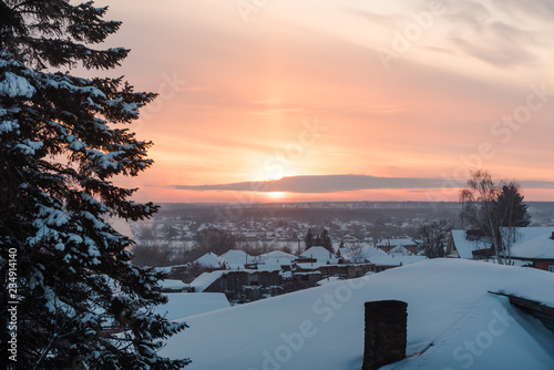 Sunset view from the window. The sun sets over the horizon. Sunset in winter among the trees and houses. - 234914140
