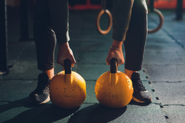 Cropped shot of male athlete doing exercises with kettle bell. Weightlifting, power lifting and cross fit equipment. Sports, fitness concept.