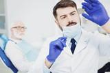 Successful male dentist fixing light