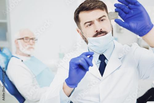 Successful male dentist fixing light - 234925774