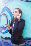 Female jogger listening music on mobile phone in front of graffiti wall © Boggy