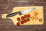 Slicing cherry tomatoes. recipe step by step farfalle with arugula leaves on chopping board flatlay on brown wood - 234932902