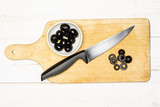 Chopping black olives step. recipe step by step farfalle with arugula leaves on chopping board flatlay on white wood - 234933360