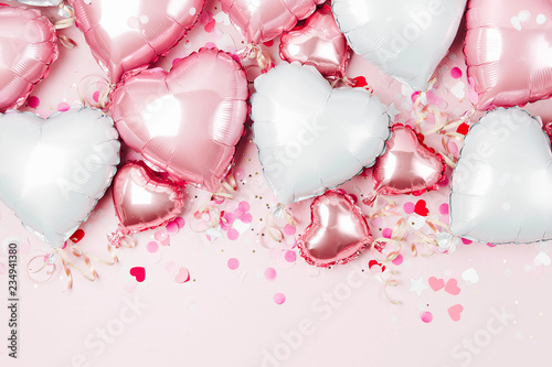 Leinwanddruck Bild Air Balloons of heart shaped foil  on pastel pink background. Love concept. Holiday celebration. Valentine's Day or wedding/bachelorette party decoration. Metallic balloon