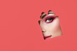 Face of a Young Beautiful Woman with a Beauty Make-up. Extension Eyelashes, Beautiful Green Eyes with Pink Shadows. Gift Box. Christmas Patterns. Red Paper
