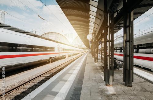 Bahn passiert Bahnhof bei blauem Himmel