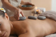 Leinwanddruck Bild - Beautiful young woman getting hot stone massage in spa salon